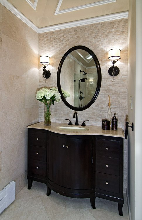 Dark wood bathroom vanity with one sink and a mirror above surrounded with sconces on either side and white flowers on the counter