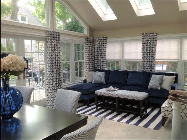 Sunroom with walls of windows, skylights a blue couch and coffee table and a dining table