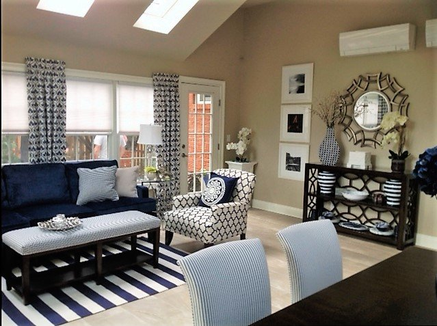 ALX Interiors Living area with a blue couch and blue and white striped rug with windows, a chair and tables and chairs