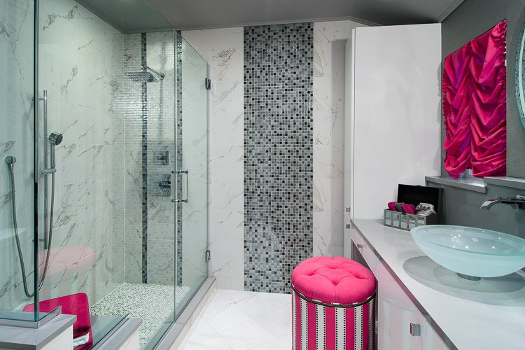Bathroom with large glass shower, vanity with vessel sink and pink pops of color
