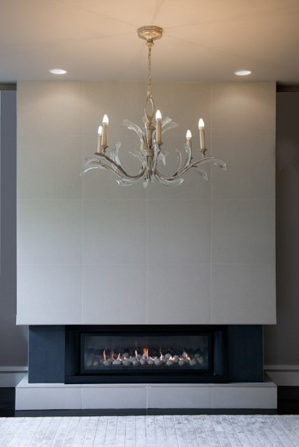 Chandelier hanging in front of a fire place