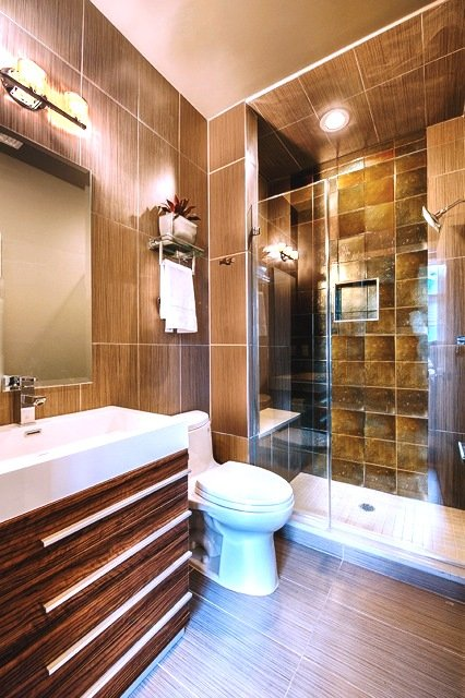 Brown bathroom with vanity, toilet and glass enclosed shower