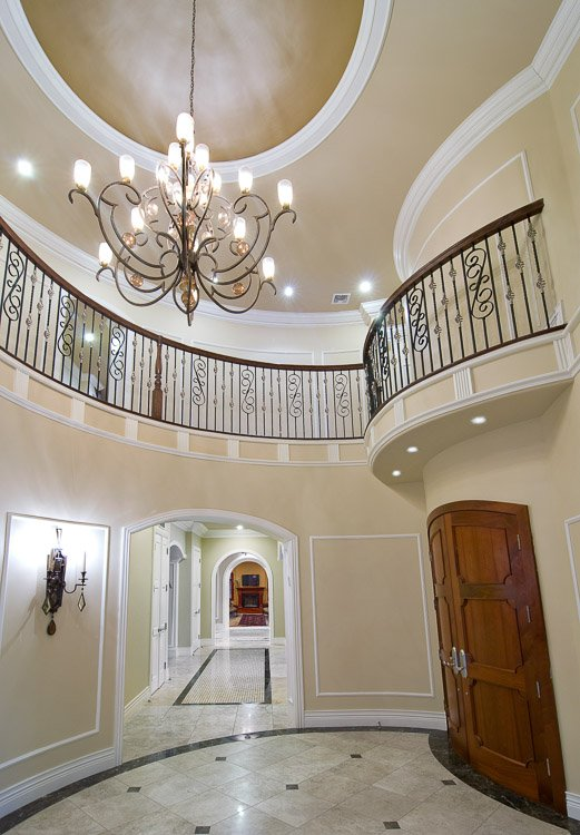 Ornate entryway with stone floor and chandelier above and a wooden door