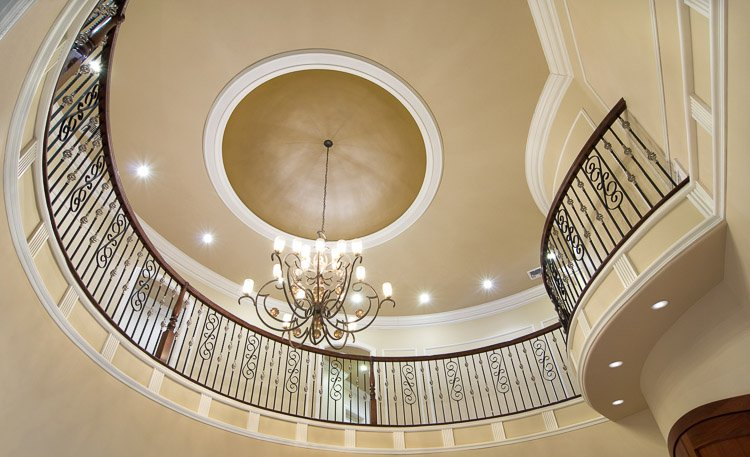 View looking up at a chandelier with ornate railings