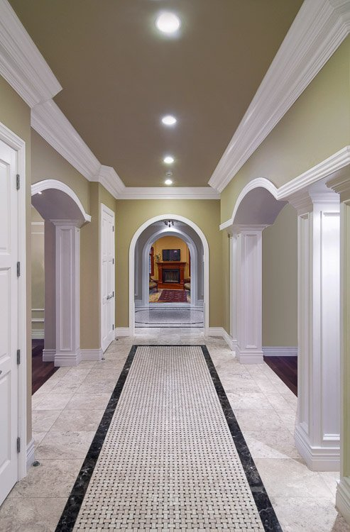 Hallway with stone floor, arches and openings into rooms off to each side