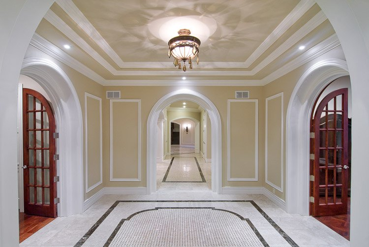 Ornate entryway with a lighting fixture, marble floor and hallway leading to various rooms