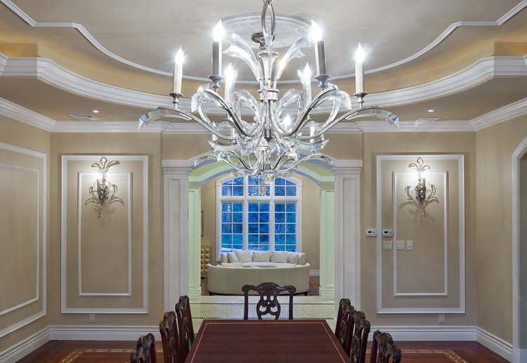Dining room with wood table, chandelier and wall sconces looking into a living room with a large window