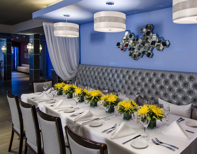 Marina Cafe table setting with chairs and banquette and yellow floral centerpieces