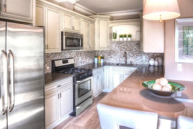 Kitchen with stainless steel appliances and white cabinets with a backsplash and island