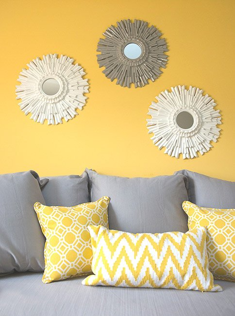 Grey couch with yellow and white throw pillows against a yellow wall
