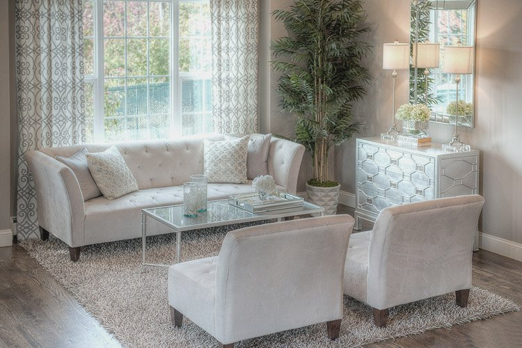 Sitting area with a couch, two chairs, a coffee table, a console with lamps and a mirror and a large window and area rug