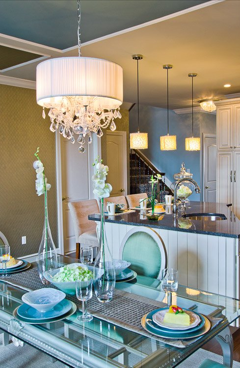 Glass dining table with blue chairs and a chandelier looking into an open concept kitchen