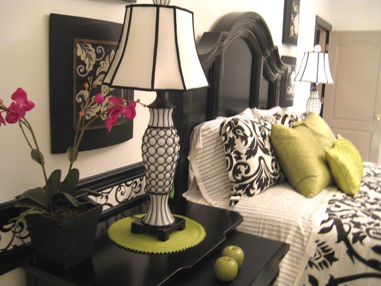 Bed with nighttable with a lamp and pink orchid and two green apples on it