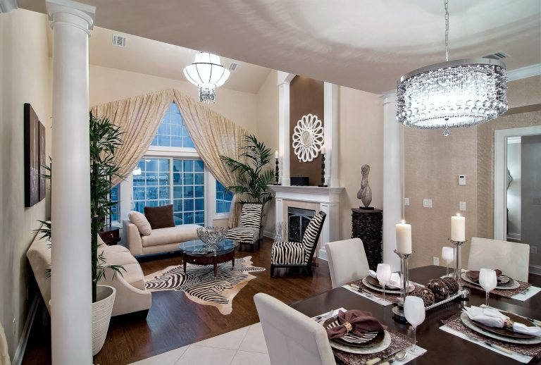 Open concept living and dining area with a table and chairs along with two white couches and two zebra chairs with a window and fireplace