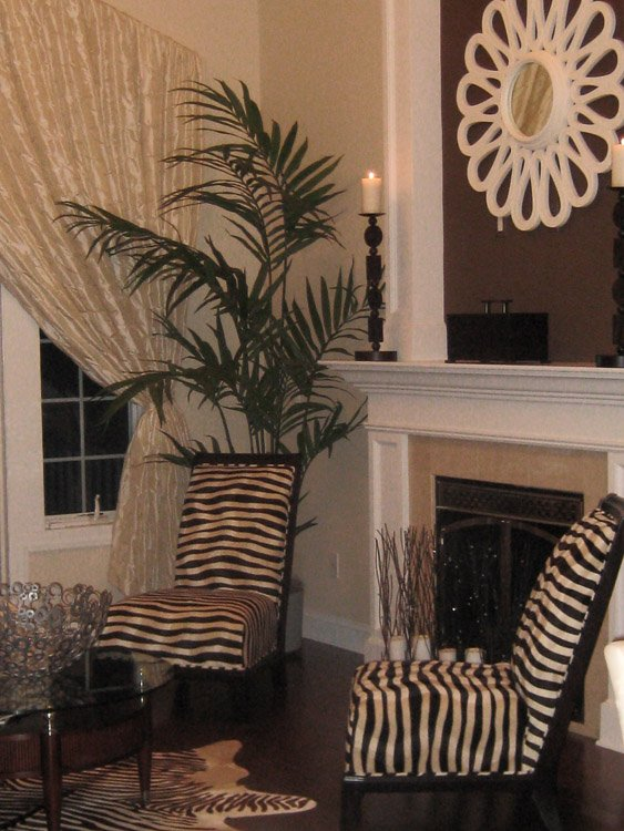 Two zebra patterned chairs in front of a fireplace