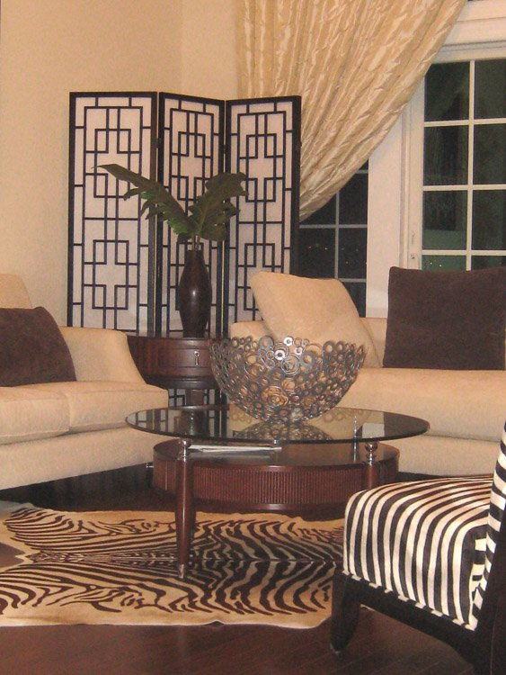 Sitting area with white couches and zebra patterned chair