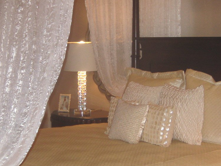 White linens on a bed with a view of a nighttable and lamp