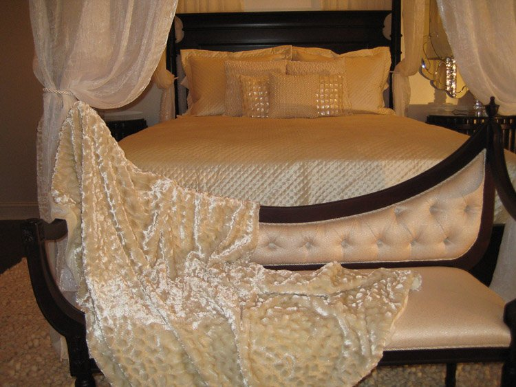 Wooden bedframe with white linens and lots of pillows and a bench at the foot of the bed