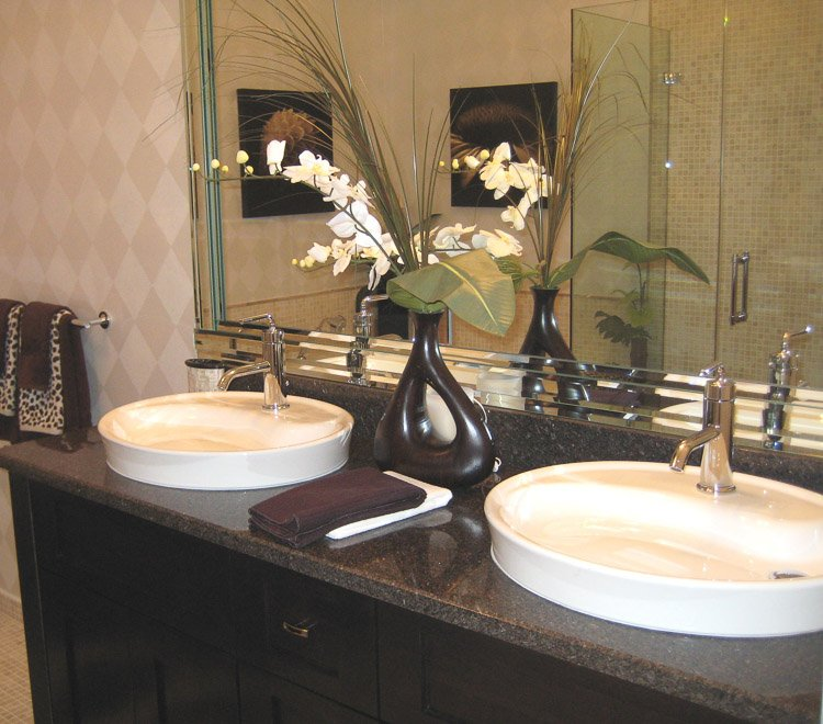 Bathroom vanity with dark countertop and dual white sinks with a mirror, towels and orchid