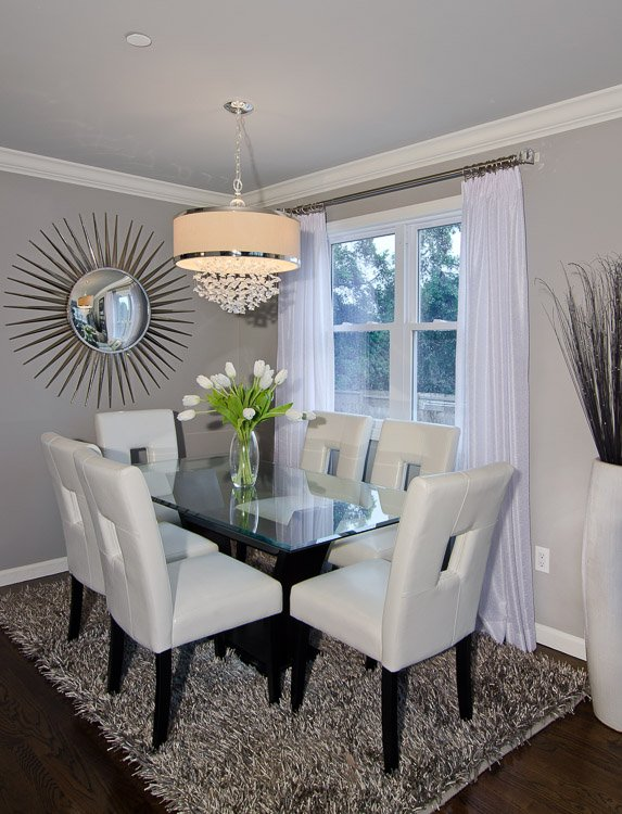Dining area with a glass table, six white chairs, a chandelier above, a mirror on the wall, a gray shag carpet blow and window with white curtains
