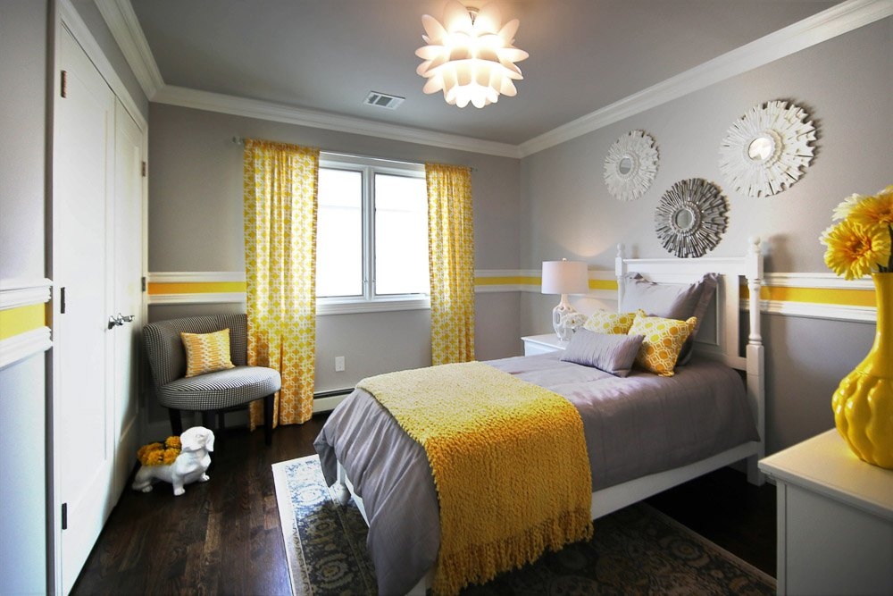 Grey and yellow bedroom with white bedframe, gray bedding and window
