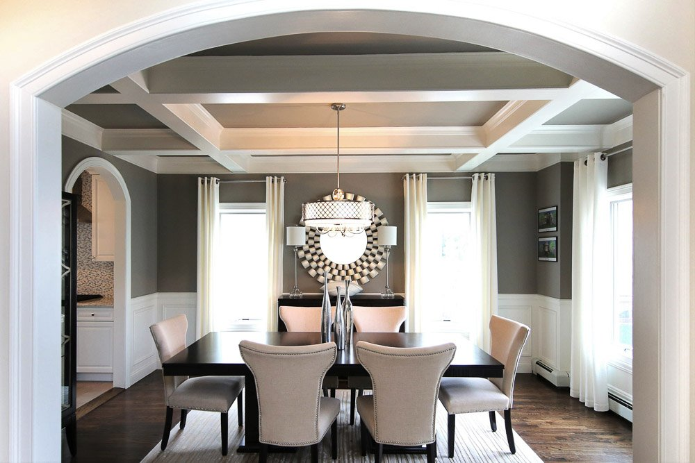 Dining room with a wood table an six white chairs
