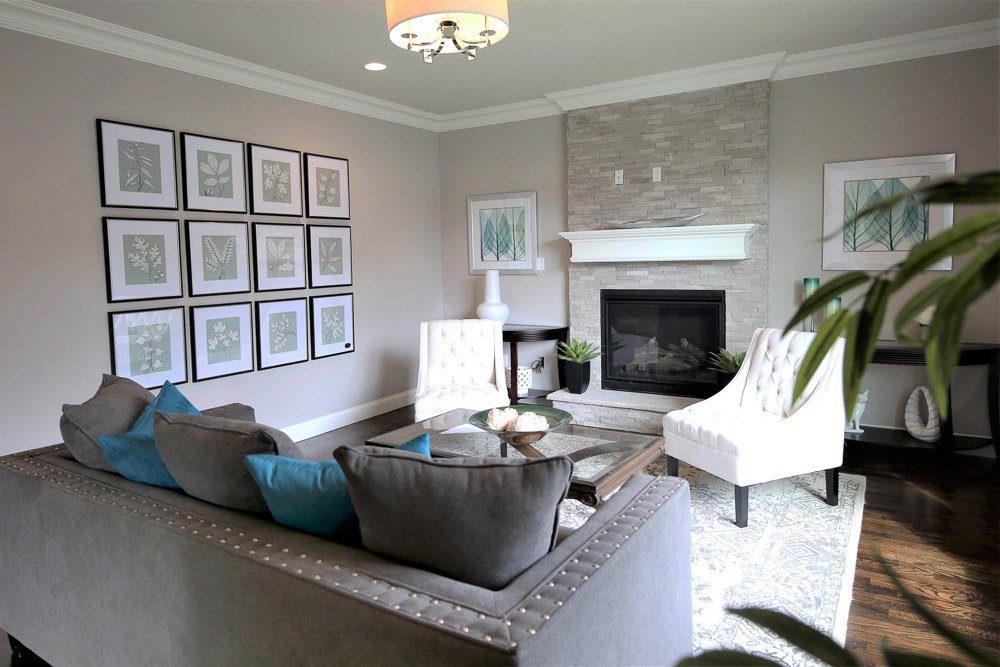 Living area with grey couch, two white chairs, fireplace with mantle and art on the walls