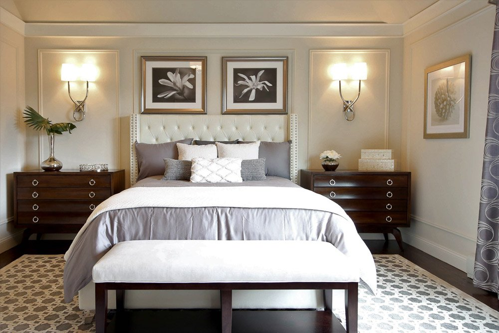 Bedroom with large bed, two nighttables and sconces with a bench and area rug