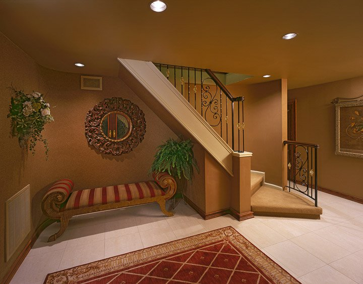 Foyer with a red and gold bench and area run and a stair case