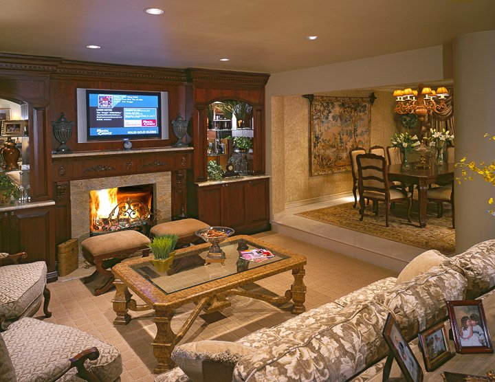 Living room with sofa, coffee table, two chairs, two small ottomans and a fireplace, tv and built ins