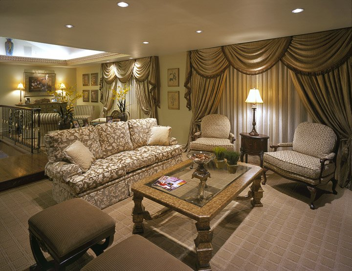 Living room with sofa, two chairs, coffee table and two small ottomans