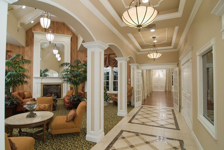 Hallway with intricate stone patterned flooring and a sitting area off to the left side