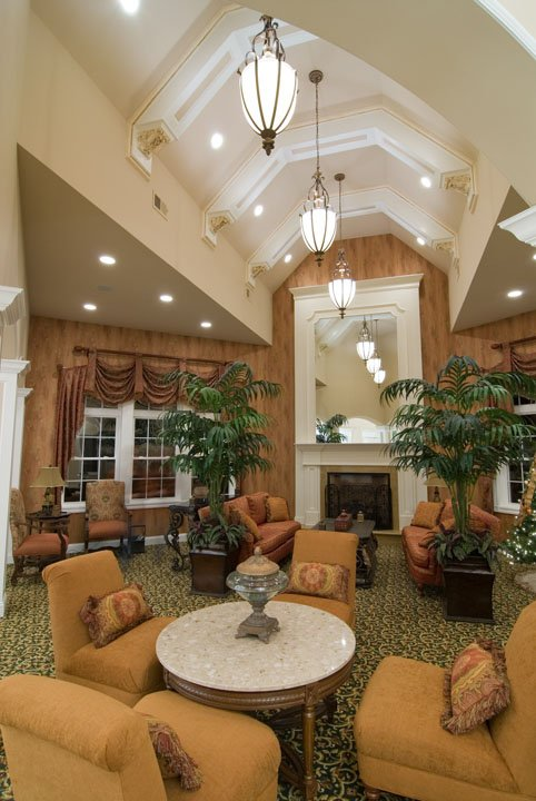 Large sitting area with many chairs, tables, couches around a fireplace with a mirror above