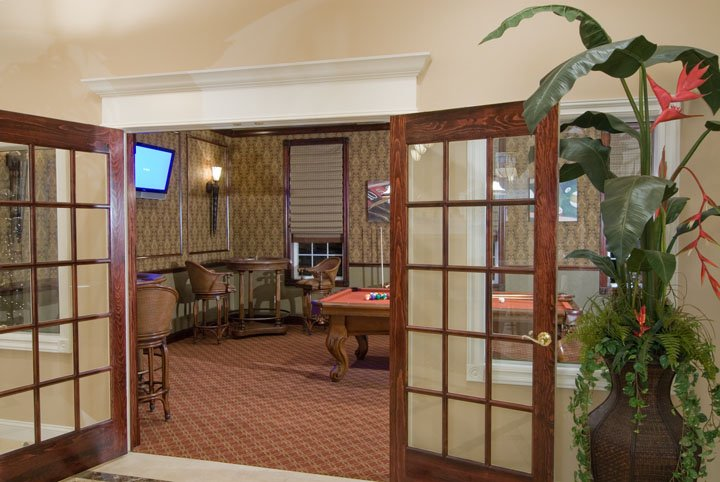 View into billiard room with pool table and tables and chairs through french doors
