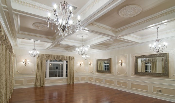 Ballroom with wall moldings, coffered ceiling with medallions, wood floor, picture window and chandelier