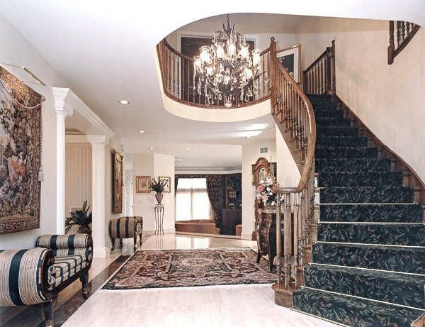Foyer with grand carpeted staircase, chandelier, area rug and two setees