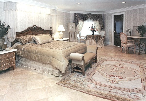 Large bedroom with a bed, table and 2 chairs, makeup vanity and chair, bench and two night tables and a rug