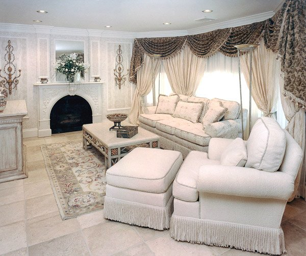 Living room with white sofa, chair, ottoman and coffee table with a fire place