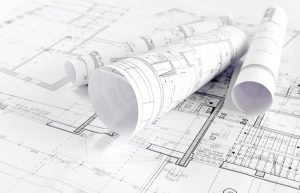 Why a Designer Should Review Your Architectural Plans three rolled up architectural plans on top of an open plan