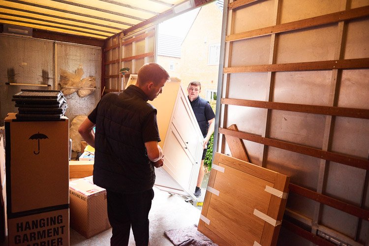 Two men moving furniture out of a moving truck