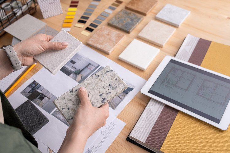 A desk top with counter top samples, an ipad and paint samples