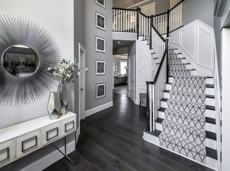 Foyer with hardwood floors, console table with mirror, artwork and a staircase