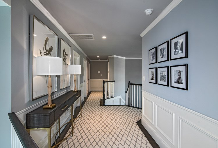 Hallway with console table, two lamps, carpet and artwork