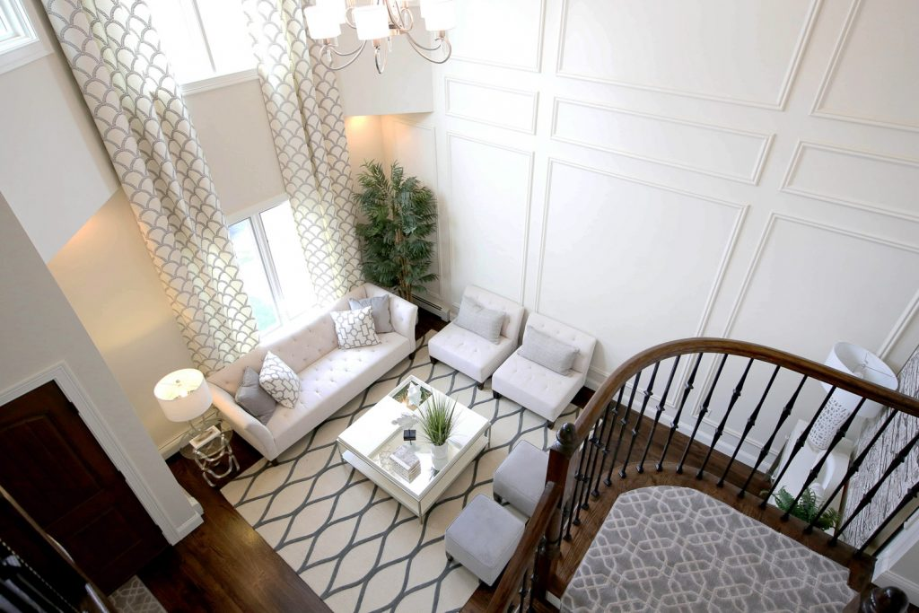 Aerial view looking down into living room with white couch and two chairs, coffee table and two ottomans