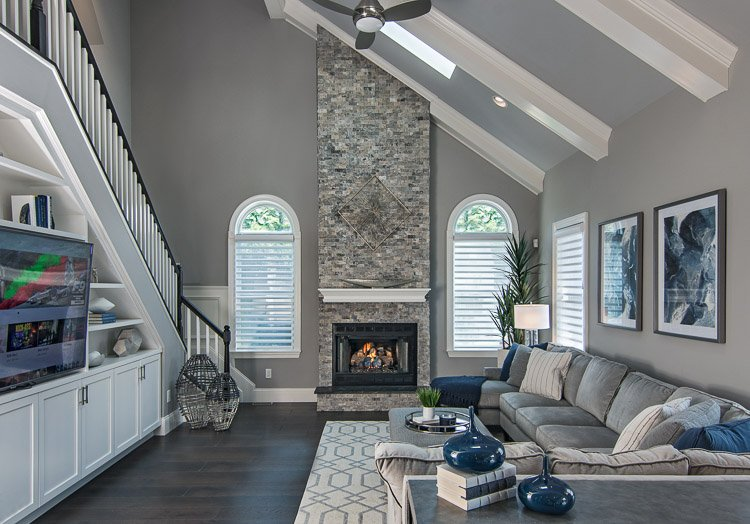 Family room with couch, tv and fireplace flanked by two windows