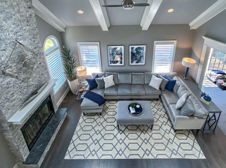 Family room with couch, ottoman, rug, fireplace and lots of windows