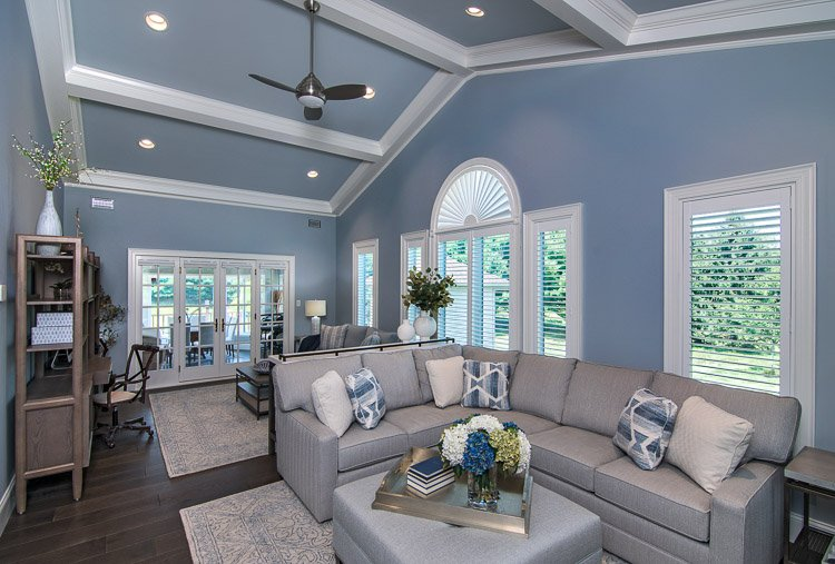 Living Room with couch, ottoman, ceiling fan and lots of windows