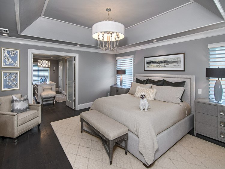 Master bedroom with bed, two nightstands, dog on bed, light fixture, carpet and bench